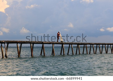 Man using fishing net on ocean pier