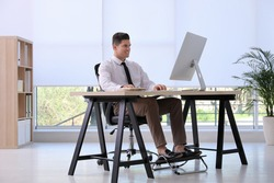 Man using footrest while working on computer in office