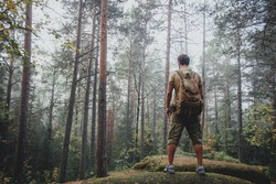 Man using hiking with backpack outdoors in woods