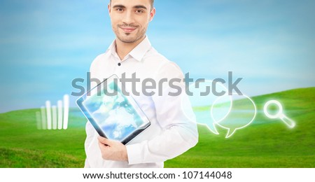 Man using his tablet computer outdoor at countryside. Mobile technology concept