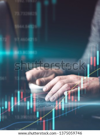 Man using laptop and analysing the financial statistics at his office. Concept of a digital diagram, graph interface, virtual screen, technical price indicator, trading online, global market.