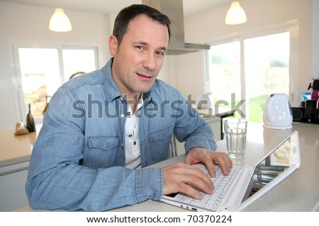Man using laptop computer in kitchen