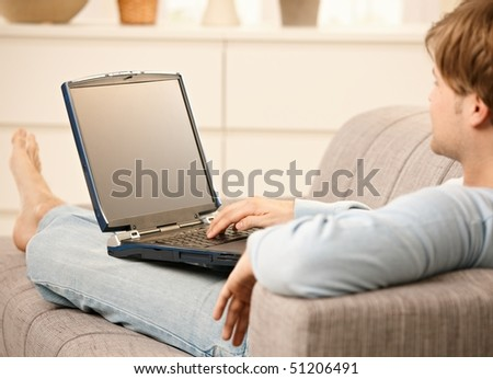 Man using laptop computer sitting on sofa in living room with feet up.