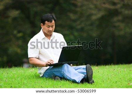 man using laptop in a garden outdoor.