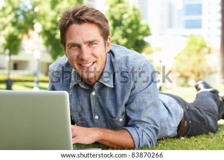 Man using laptop in city park