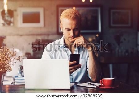 Man using laptop in coffee shop.