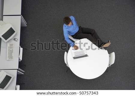Man Using Laptop in computer room, overhead view - stock photo