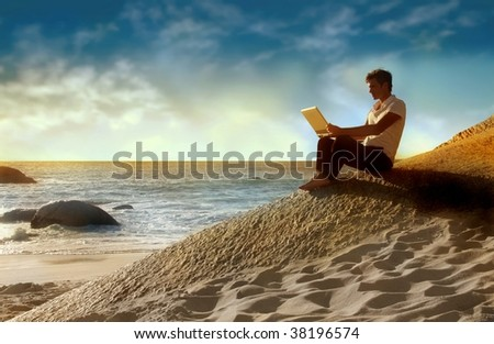 man using laptop on the beach at the sunset