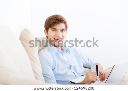 man using laptop shopping on line sitting on a sofa happy smile, hold credit card, young handsome guy smile relaxing on couch at home