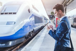 man using mobile application on his smartphone at train station, business travel