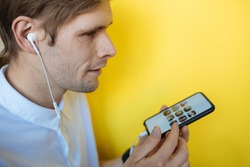 Man using mobile phone next to the yellow background. Social media screen. Clubhouse the voice-only social media app. Clubhouse, a social platform built around drop-in audio chat. Using social app