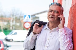 man using mobile phone on the wall