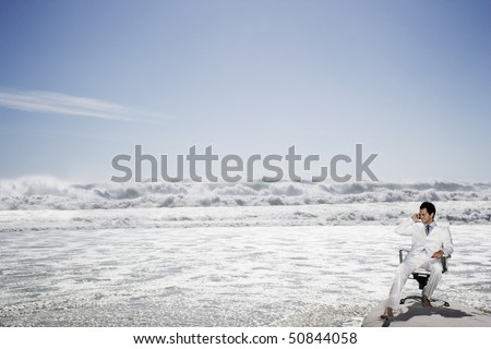 Man using mobile phone sitting on office chair on beach