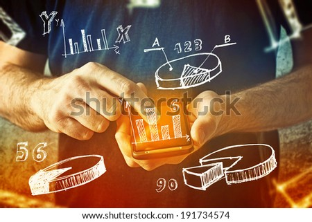 Man using mobile phone with drawings of charts and other infographics in note pad. Close up image with selective focus. Business situation. - Shutterstock ID 191734574
