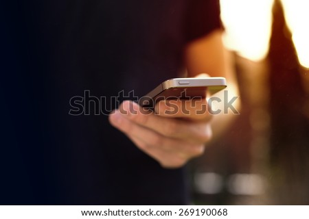 Man using mobile smartphone - focus on top of the phone