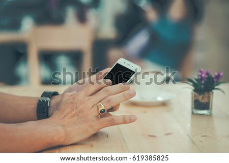 Man using mobile smartphone in the coffee shop #619385825