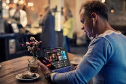 Man using modern tech while sitting in cafe