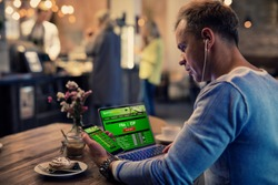 Man using online sports betting services on phone and laptop