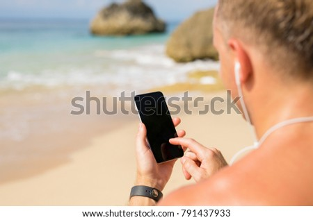 Man using phone on the beach #791437933