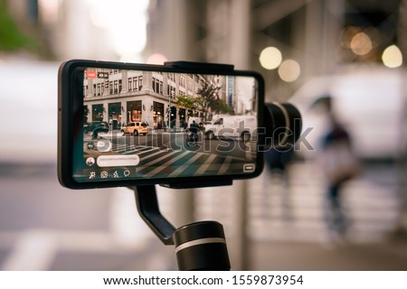 Man using phone with stabilizer and taking pictures and live video in New York city. Vlog, video blogging, street photography concept.