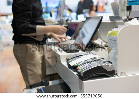 Man using pos terminal at the shop (paying credit card for purchases)