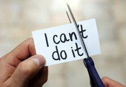Man using scissors to remove the word can't to read I can do it concept for self belief, positive attitude and  motivation