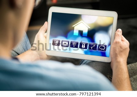 Man using smart home application in tablet to control house appliances. Internet of things (IOT) and remote controller app on smart device. Modern futuristic technology. #797121394