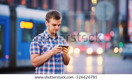 Man using smart phone at night in city. Handsome young Business Man texting, talking on smartphone outdoors. Professional millennial with cellphone, blurred Night Busy Street lights background #526626781