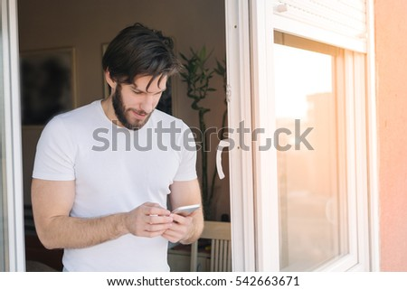Man using smart phone by the window #542663671