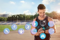 Man using smart watch during training outdoors. Icons near hand with device