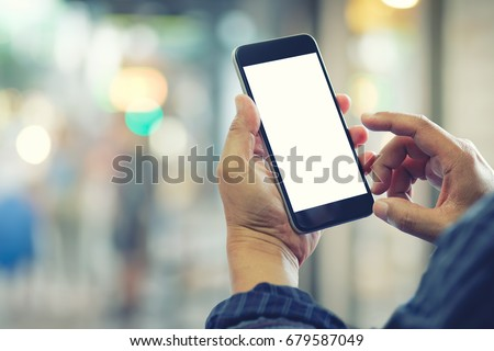 Man using smartphone at street night. Blank screen mobile phone for graphic display montage.