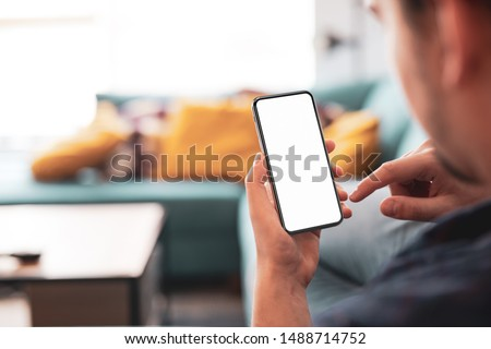 Man using smartphone frameless mockup blank screen in home interior