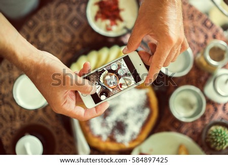 man using smartphone in cafe. smartphone white screen. hand holding smartphone. Hands with the phone close-up pictures of food. Pancake, cereal and coffee for breakfast. vintage tone.