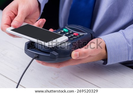 Man using smartphone to express pay on a wooden table #269520329