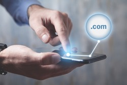Man using smartphone with a .com domain button.