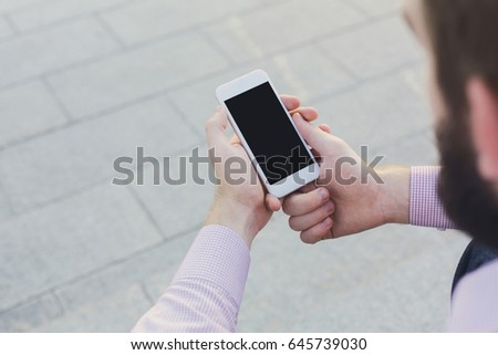 Man using smartphone with blank screen, mockup. Top view on unrecognizable guy reading information in mobile phone, copy space for advertisement. #645739030