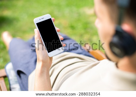 Man using smartphone with blank screen while listen to the music.