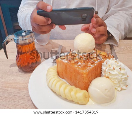 Man using smartphones to take pictures of honey toasts with bananas and ice cream at modern wooden tables in coffee shops.