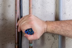 Man using strength to turn a water valve on a pipe gripping it with his hand indoors in a utility room in a close up view