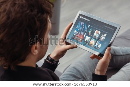 Photo of  Man using tablet for watching VOD service. Video On Demand television concept