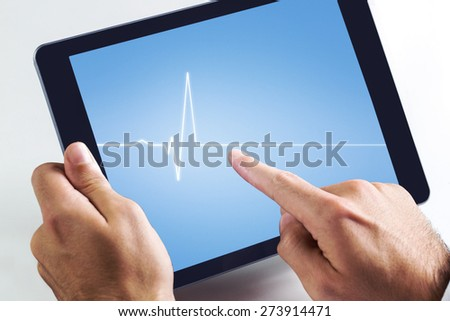 Man using tablet pc against medical background with blue ecg line