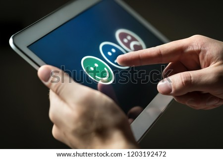 Man using tablet to give review, opinion and feedback to survey, poll or questionnaire for user experience or customer satisfaction research. Technology for service quality control. Rating concept.
