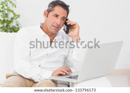 Man using the moblie phone and his laptop on couch