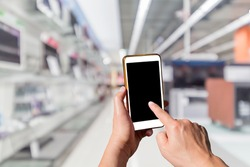 Man using touch screen mobile phone with blurry image of Electrical appliance stores