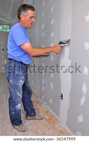 Man using trowel to finish seam between drywall panels