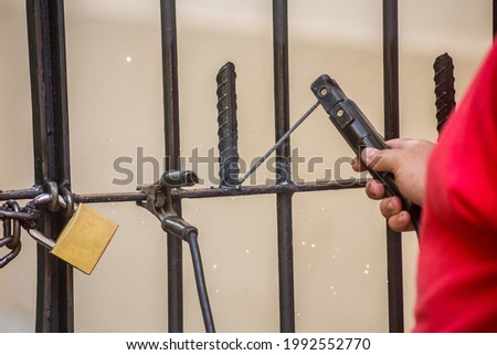 man using welding a piece of iron in an outdoor gate in Rio de Janeiro. Foto stock ©