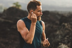 Man using wireless earphones on running outdoors. Active lifestyle concept.