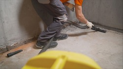 Man Vacuuming a Construction Site. Closeup of a cleaner in special clothes and rubber gloves holds a brush from an industrial professionally vacuum cleaner. A worker removes building dust with a