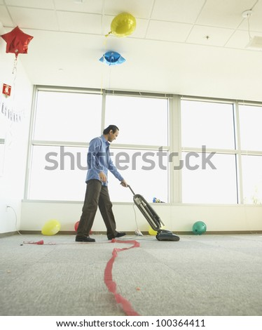 Man vacuuming after office party