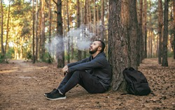 Man vaping outdoor. bearded young man having rest and sitting under the tree in forest.